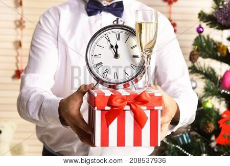 Male Hands Hold Present Box With Champagne Glass And Clock