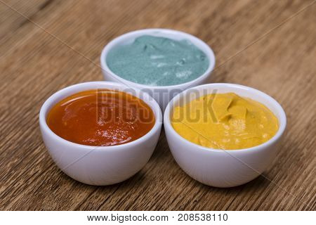 Red Tomato Sauce, Turmeric Sauce And Spirulina Sauce On The Wooden Background