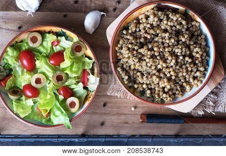 Couscous and lettuce salad tomatoes and olives. Delicious lunch in different countries of the world