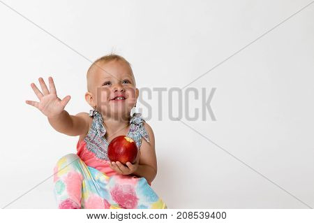 Studio shot of smilling toddler girl is sitting gesticulating and holding red apple