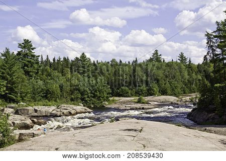 Wide view of a some small rapids off a rock shoreline surrounded by trees and greenery at Pabineau Falls near Bathurst, New Brunswick on a bright sunny day with blue skies and clouds in August.