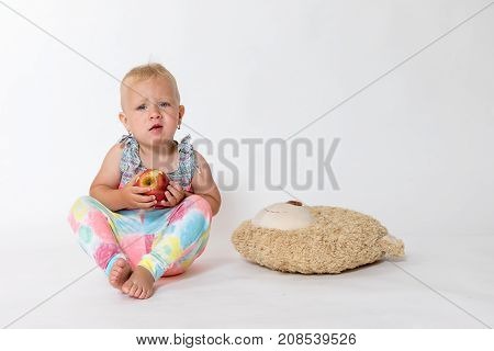 Studio shot of whole figure of angry toddler girl sitting and holding red apple. Plush toy is lying next to the girl.