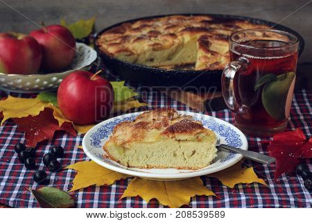 Pie of apples. Charlotte. A piece of cake on a plate tea Cup and red apples on the table with a tablecloth in a cage. Food still life.