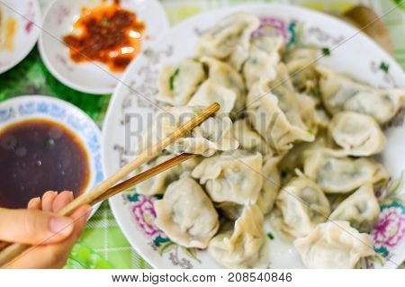 Chopsticks Pick Up Boiled Chineses Dumplings. Red Chili and Soy Sauce Blurred at Background