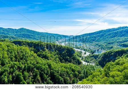 A view of the valley of the river covered with forest in the Caucasian mountains near Sochi. Trout farming. The road going to Krasnaya Polyana. View of the valley of Mzymta from the suspension bridge.