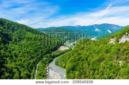 A view of the valley of the river covered with forest in the Caucasian mountains near Sochi. The valley of the river Mzymta. The road going to Krasnaya Polyana. View of the valley of Mzymta from the suspension bridge