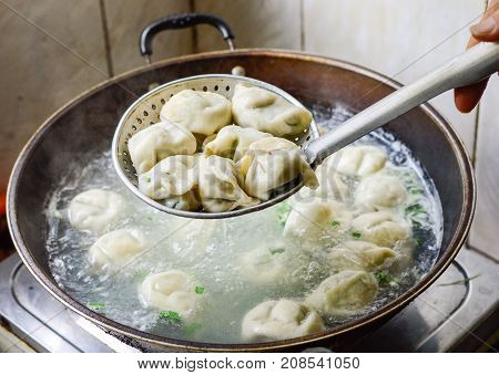 Chinese Family Cooking Boiled Dumplings. The dumplings are picked up from the wok.
