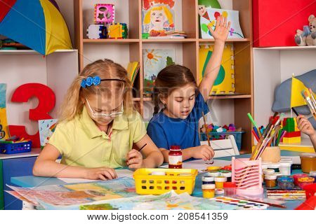 Small students painting in art school class. Schoolgirl raises her hand to answer.