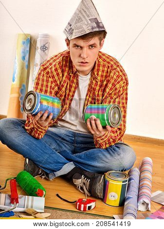 Repair home man holding paint bank. Tired and frustrated mad male in newspaper cap renovation apartment. Profitable loan for repairs. Worker-builder student. Choice of materials for construction.
