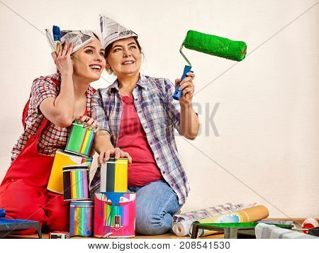 Repair home women holding bank with paint for wallpaper. Elderly mother and daughter renovation apartment on isolated. Tired workers sit on floor and rest from work done. Profitable loan for repairs.