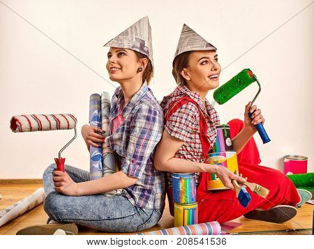 Repair home women holding painting tools roller for wallpaper and paint bank for wall. Happy girls wearing newspaper hat renovation apartment in room. Profitable loan for repairs.