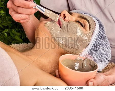 Collagen face mask. Facial skin treatment. Elderly woman 50-60 years old receiving cosmetic procedure in beauty salon. Healing clay for the face. Therapeutic mud for home masks.