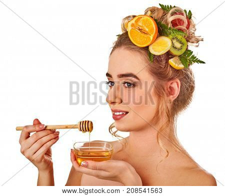 Honey facial mask with fresh fruits for hair and skin on woman head. Girl with beautiful face hold honeycombs for homemade organic skin and hair therapy. Acceleration of hair and eyebrows growth.
