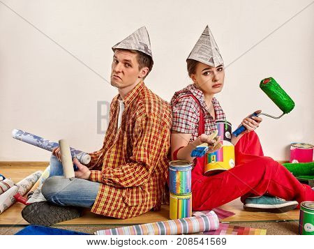 Repair family by happy couple building home. Quarrel family because of renovation in new apartment. Mad woman and man in newspaper cap. Unprofitable loan for repairs.