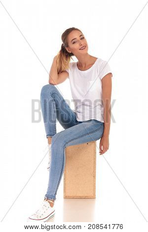 smiling casual woman playing with her ponytail sitting on wooden box on white background