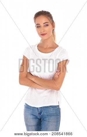 smilling and confident young casual woman standing with arms folded on white background