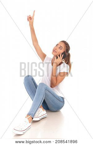 smiling woman talking on the phone is pointing up on white background