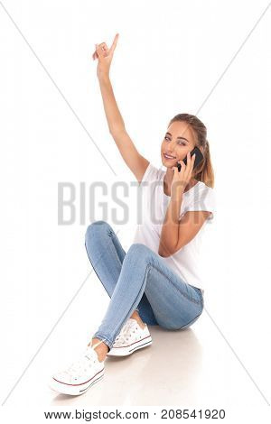 smiling casual woman points up and speaks on her mobile phone on white background