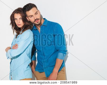 man leaning head on confident woman's shoulder and looks to side in studio