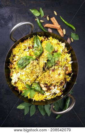 Indian chicken biryani with nuts and raisins as close-up in a korai