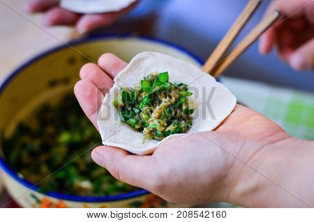 Hand Holding Chinese Dumpling Skin with Pork Chive Filling on Top. Chinese Family Making Dumplings at Home. The Dumpling Fillings and Chopstick Blurred at Background.