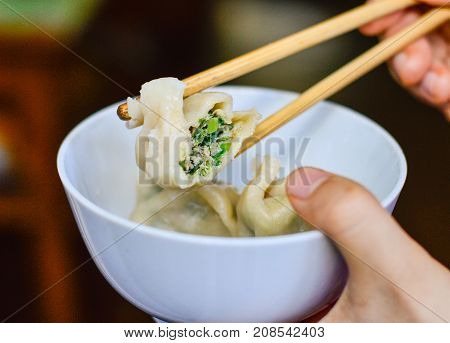 Chopsticks Pick Up an Opened Chinese Dumpling from a Bowl. It Shows the Meat Veggie Fillings Inside the Dumpling.