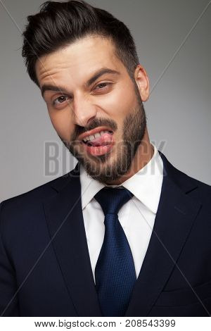 weird business man sticking out his tongue on grey background