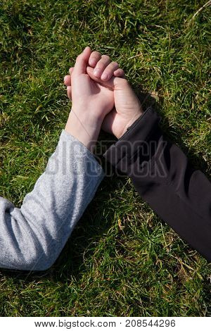 Two female hands, mother and saughter holds each other hands lying in grass