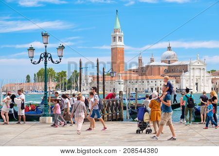 VENICE,ITALY - JULY 26,2017 : Tourists walking next to the Grand Canal next to St Mark's Square in Venice