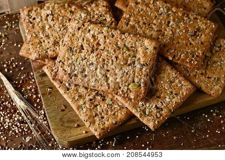 high-angle shot of some brown crackers topped with different seeds on a chopping board placed on a rustic wooden table