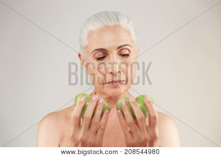Beauty portrait of an attractive half naked elderly woman looking at two slices of green apple isolated over white background
