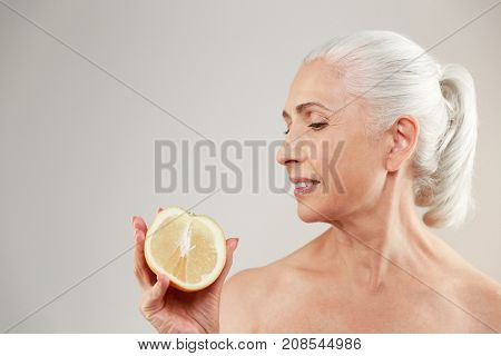 Beauty portrait of an attractive half naked elderly woman showing a sliced orange and looking away isolated over white background