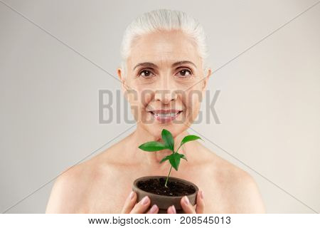 Beauty portrait of a joyful half naked elderly woman holding plant flower and looking at camera isolated over white background