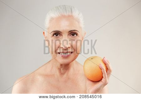 Beauty portrait of a smiling half naked elderly woman holding an orange and looking at camera isolated over white background