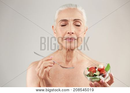Beauty portrait of a satisfied half naked elderly woman eating healthy greek salad from a bowl isolated over white background