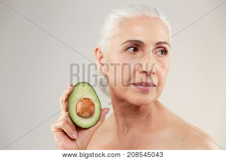 Beauty portrait of an attractive half naked elderly woman showing a sliced avocado and looking away isolated over white background