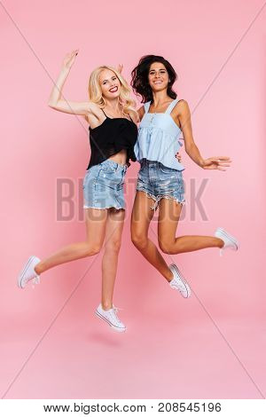 Full length image of two cheerful women in summer clothes rejoice and jumping while looking at the camera over pink background