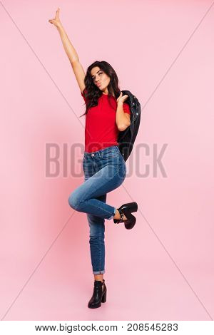 Full length image of pretty brunette woman posing in studio and showing peace sign while looking at the camera over pink background