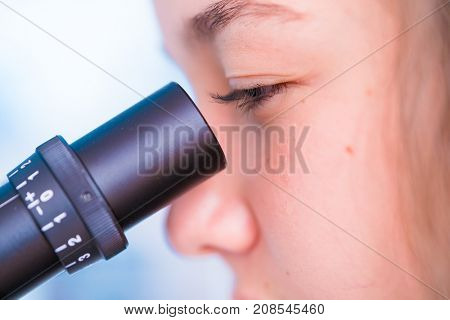 schoolgirl girl looks through a microscope at a biology class at a gymnasium