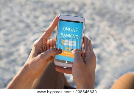 Online banking text on blue mobile screen against hands of man using mobile phone at beach