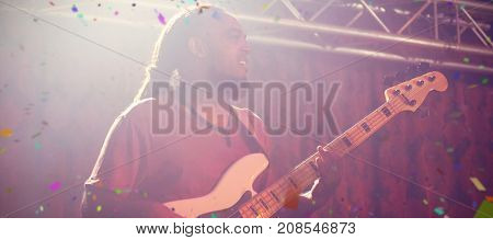 Flying colours against male guitarist playing guitar on stage