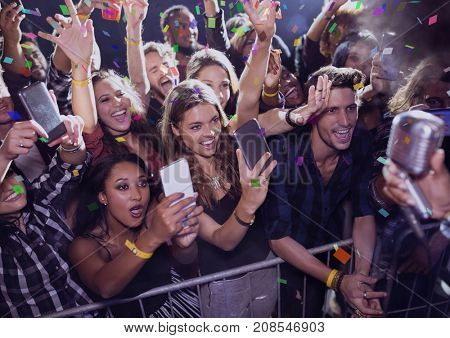 Digital composite of People having fun and making photos at a concert with 3D confetti