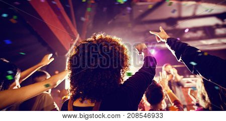 Flying colours against people enjoying music concert at nightclub