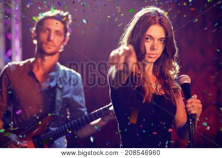 Flying colours against portrait of singer with male guitarist performing at nightclub