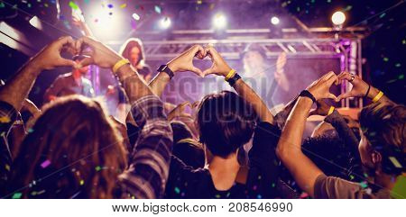 Flying colours against crowd making heart shape with hands during performance