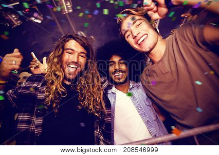 Flying colours against male friends enjoying at nightclub during music festival