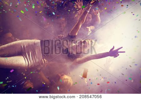 Flying colours against high angle view of crowd lifting female performer at club