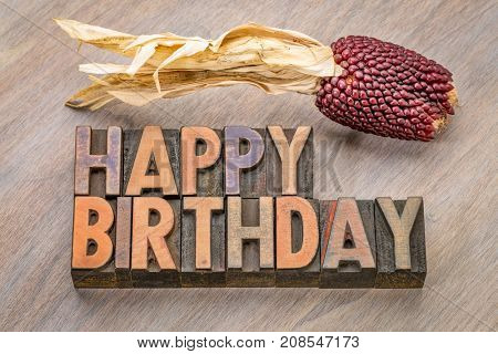 Happy Birthday greeting card in vintage letterpress wood type against grained wood with a decorative strawberry corn