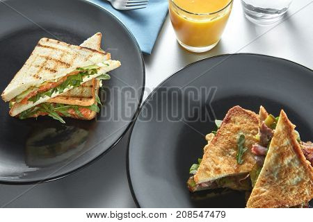 Two black plates with sandwiches and juice.
