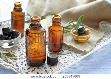 Glass bottles with olive oil on white tray